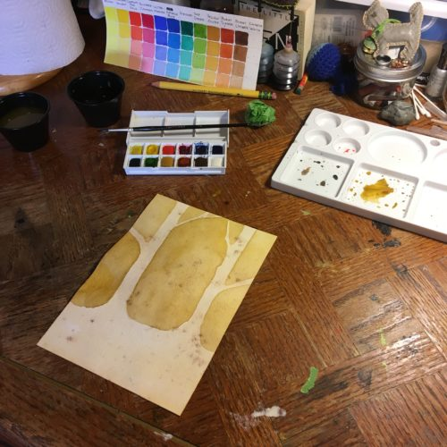 Watercolor painting on artist's table.